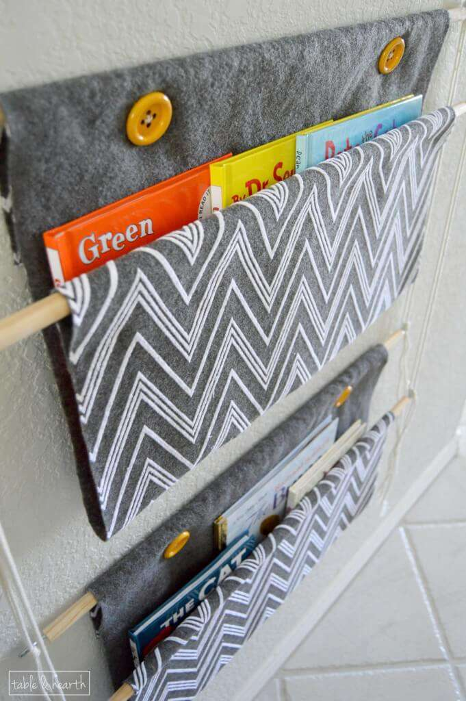 Need an easy, customizable way to store children's books?? This easy holder only uses rope, wood dowels, and some fabric and can be hung anywhere!