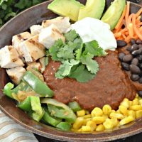 Restaurant flavor the easy way! These easy to make enchilada bowls are topped with a traditional and delicious mole sauce. Find the recipe at www.tableandhearth.com