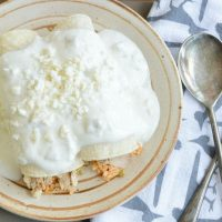 Green Chile Rice Enchiladas - These simple enchiladas are filled with green chiles and spanish rice, then topped with a delicious sour cream sauce. www.tableandhearth.com